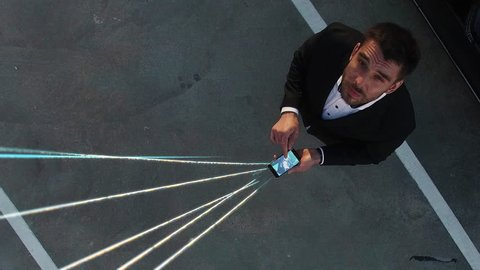 Big City Businessman Uses Smartphone, Stands on Skyscraper Roof: Visualization of Information Flows and Lines Flying from Mobile Phone into Global Network. Top Down Aerial Elevating Drone Shot.