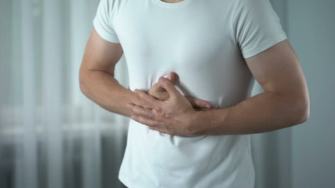 Man feeling stomach pain at home, gastritis symptom, peptic ulcer, pancreatitis