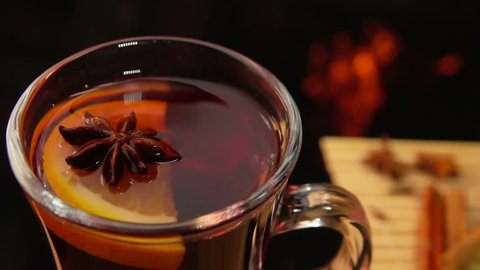 Cinnamon sticks falling from above in a nice mug of mulled wine, slow motion