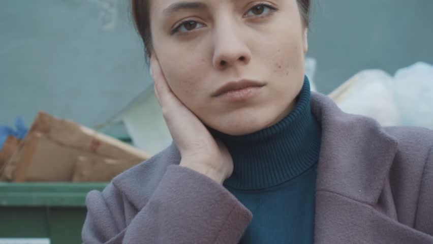 The girl stands against the background of trash. Face close up (slow)   Shutterstock HD Video #1021350202