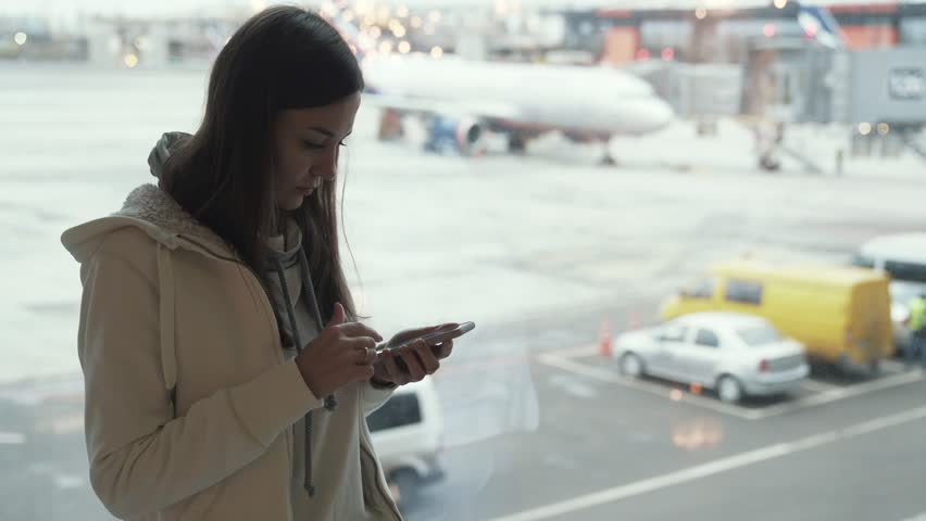 Attractive girl standing at window in airport terminal and using phone in background of airplane. Traveler in white jacket in airport. Concept journey, trip, tour, flight, aircraft, arrivals, lounge | Shutterstock HD Video #1021366732