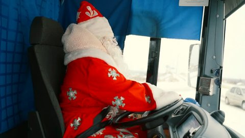 Santa Claus is driving a car. Father christmas drives a truck.