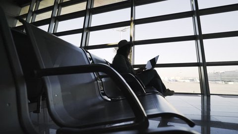Side view young lady in casual wear and hat using laptop and sitting on seat near window in airport lounge