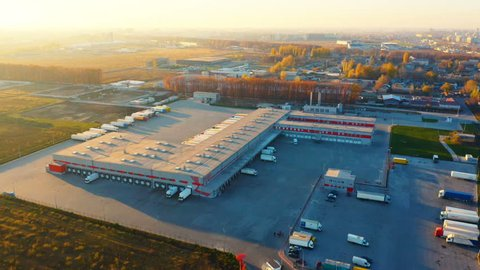 Aerial circling view of a logistics center with warehouse, loading hub with many semi-trailers trucks  load/unload goods at sunset