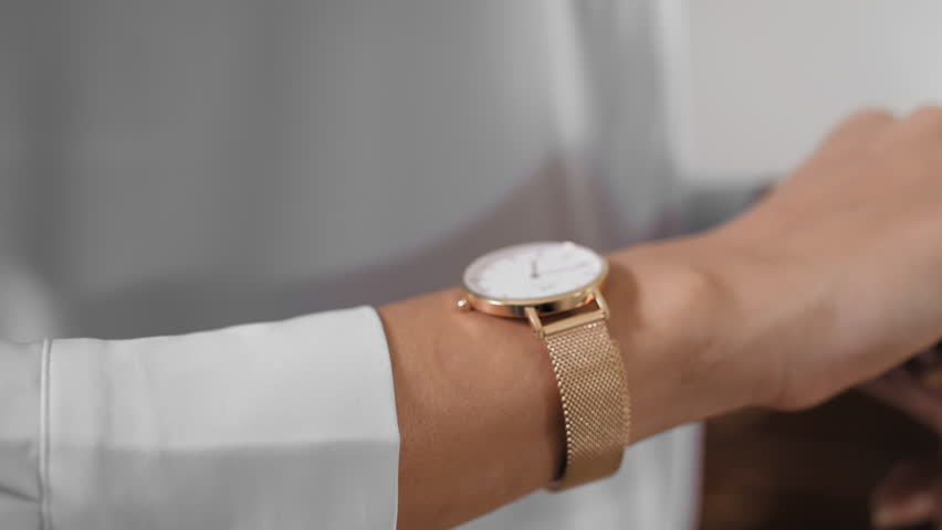 Gold watch in a women wrist. Gold watch in a women wrist, hand, looking at clock, preparing for an event. 4k footage