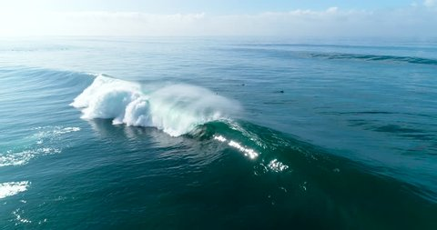 Slow motion aerial view of large blue ocean waves crashing on sunny day