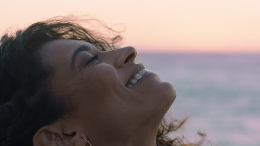 Close up portrait of beautiful hispanic woman looking up exploring mindfulness contemplating spirituality with wind blowing hair enjoying peaceful seaside at sunset | Shutterstock HD Video #1021487332