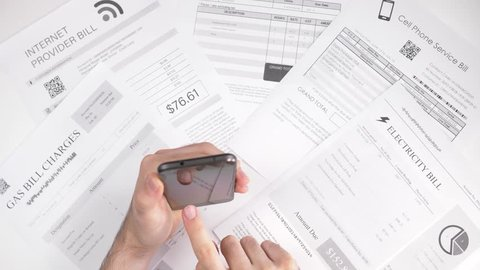 Paying bills using asmartphone. Online utility bills payment concept.The information on the bills are fake, placeholder name is use.
