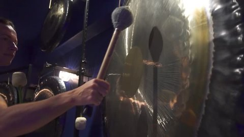 Woman is playing big gongs during healing yoga gong practice. Sound therapy. Mindfulness, tranquility and harmony.