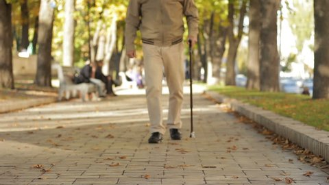 Fall, weak grandad limping slowly, carefully along parkway, leaning on old cane