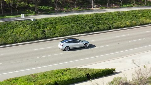 Newport Beach, CA / USA - December 27th 2018: Aerial view of Tesla Model 3 Performance electric vehicle or EV car driving up a street or road on sunny day.