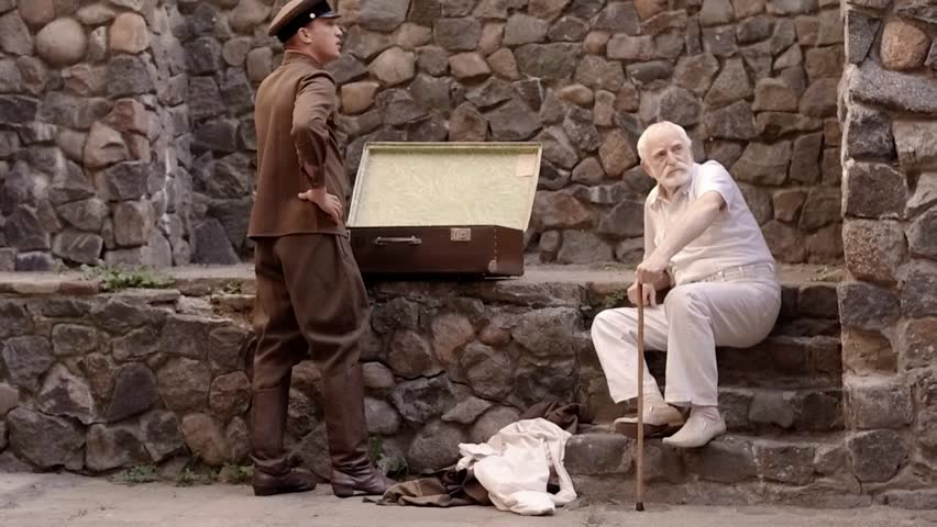 Angry NKVD soldier interrogates a miserable, bearded, gray-haired old man on the street, a soldier mocks his grandfather, tortures of the NKVD, the old man fears for his life, wartime