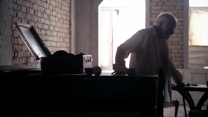 An old man of aristocratic appearance, but a bit disheveled, collects an old suitcase on the piano, a 20th century storyboard, a production video, an aristocrat in an old castle | Shutterstock HD Video #1021575202