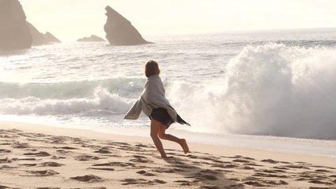 Running child girl along waterline huge waves splashing on the Atlantic shore background