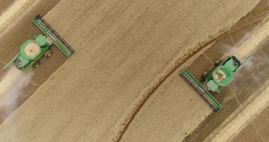 4K spectacular straight down zoom out rotating aerial view of two combine harvesters harvesting wheat | Shutterstock HD Video #1021626172