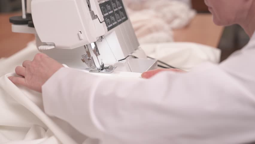 A close up side view of a seamstress finishing stitching white fabric on the sewing machine. Another tailor is sitting at the table and sewing beads down the veiling cloth to make a wedding dress | Shutterstock HD Video #1021627822