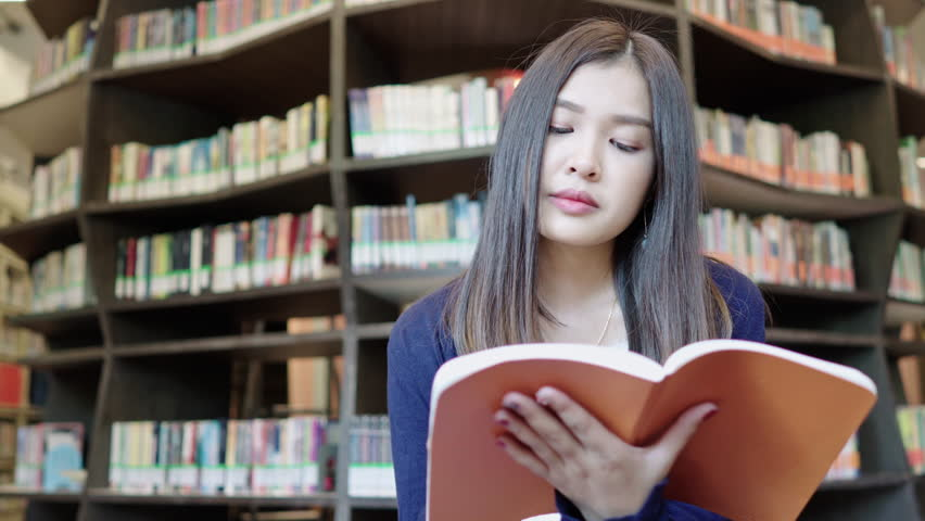 Asian girl student siting at the front of bookshelves and reading book in the university library. Education concept. | Shutterstock HD Video #1021668502