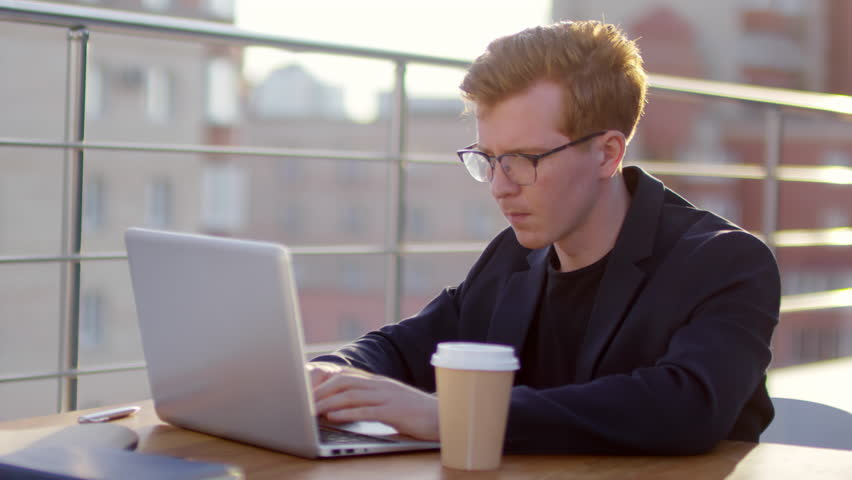 Young redhead businessman in eyeglasses sitting at table with coffee cup on it and typing on laptop while working outdoor on rooftop on sunny day | Shutterstock HD Video #1021685602