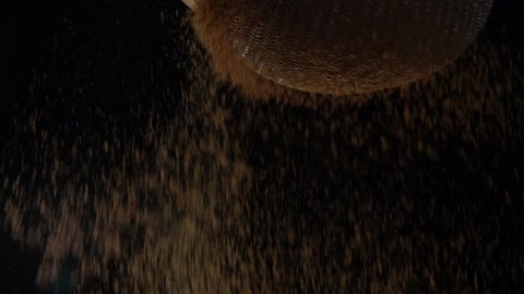 Cocoa powder on a colander in black background - Slow motion
