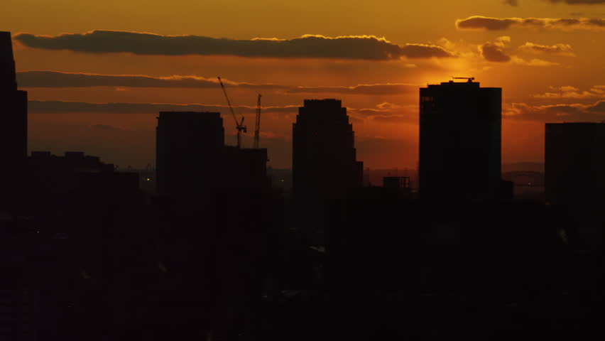 Shot on 4k RED camera on helicopter. Aerial view of silhouettes of buildings and skyscrapers in downtown Manhattan, New York City with soft sunset sky.