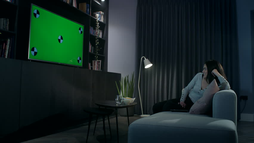 Attractive young woman in her apartment  at night watching a large flat screen tv. She changes the channel using the remote control | Shutterstock HD Video #1021744222