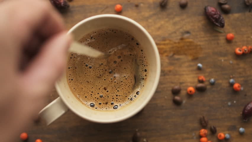 Male hand steering coffee in a cup with spoon, top view slow motion | Shutterstock HD Video #1021752532
