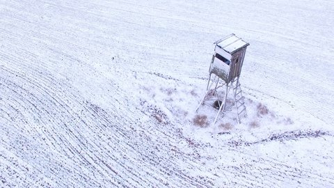 Camera flight around deer-stand or watch tower for hunting of boars in snowy fields. Wild boar is very dangerous pest in Czech agricultural landscape. Agriculture in Czech Republic, European Union.