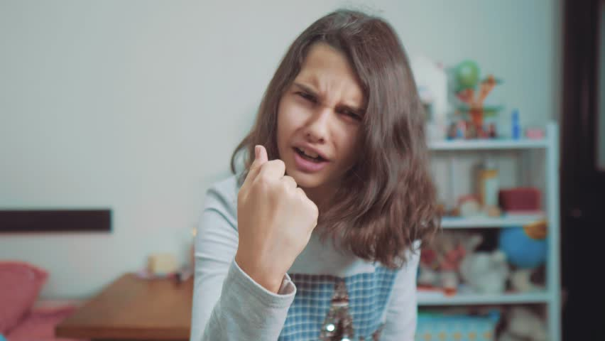 little teenage girl angry gesture fist threat. slow motion video. Girl kid  threatening with fist . teen girl asks for silence. lifestyle Kids  aggression ...