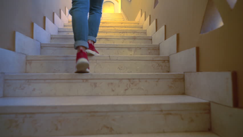 Person walking up a fight of narrow wooden indoor stairs at home in a low angle view of the legs in denim jeans