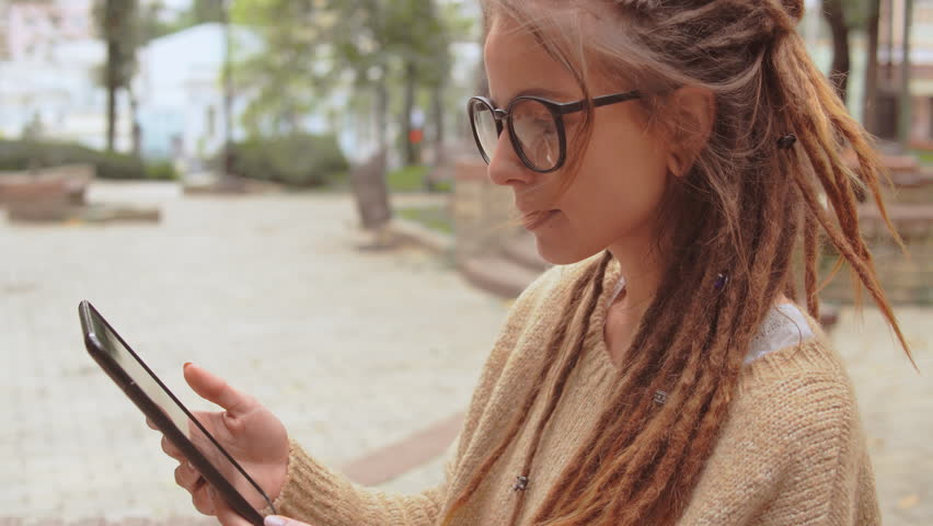 Side view smiling young caucasian woman with dreadlocks and eyeglasses using app on digital tablet swipe left and right | Shutterstock HD Video #1021785442