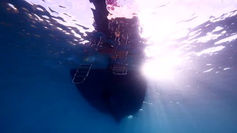 scuba diver jumps in the water from boat underwater