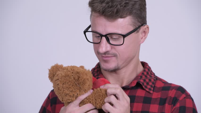 Bearded hipster man holding teddy bear and acting childlike