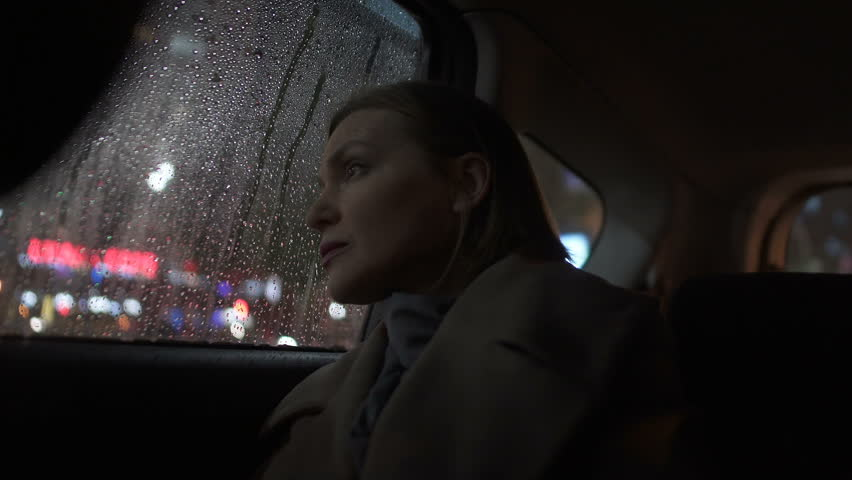 Sad woman riding taxi in evening, looking into car window on rain, city lights | Shutterstock HD Video #1021901602