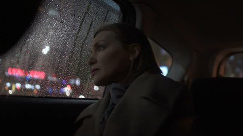 Sad woman riding taxi in evening, looking into car window on rain, city lights