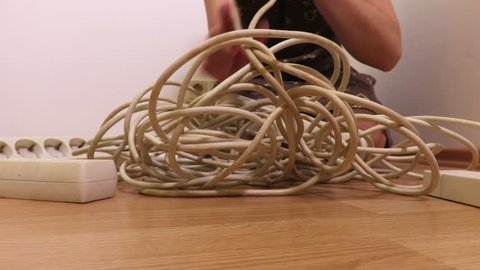 Woman try to fix old electrical extension strip cords
