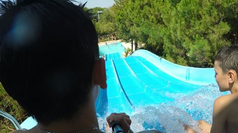 Original back view of sportive young man riding a water flume with several kids nad taking a selfie while falling in a pond in aqua-park in summer