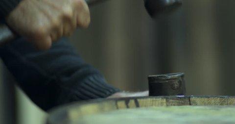 Cooper craftsman hammers iron hoops onto whiskey barrel keg
