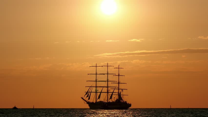 During sunset Beautiful silhouette sailing vessel in the sea. three-masted ship floats on the high seas | Shutterstock HD Video #1021984822