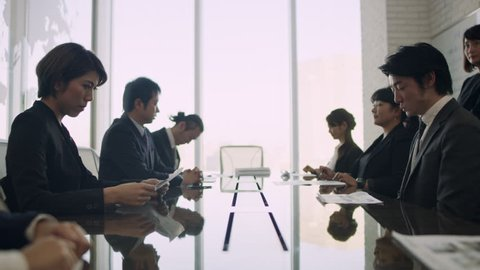 Medium shot on 4k RED camera on a gimbal. Group of Japanese business people celebrate after boss sits down and delivers good news in a small business office with soft natural lighting.