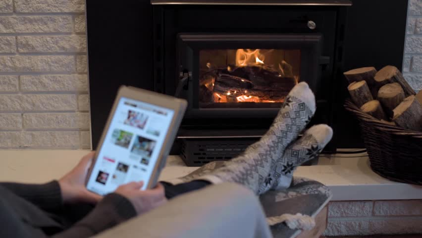 Woman on tablet in front of fire place in low light | Shutterstock HD Video #1021998022