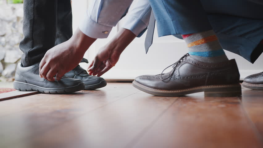 Close up of father wearing shirt and tie, brogue shoes and striped socks kneeling down on one knee to fasten the straps on his sons shoes before school, low section, close up of feet