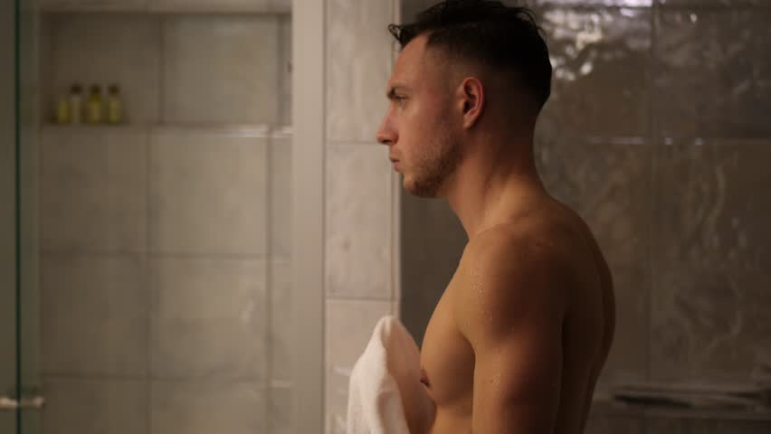 Shirtless muscular handsome young man looking at camera in bathroom in the morning, wearing only white towel around waist | Shutterstock HD Video #1022060002