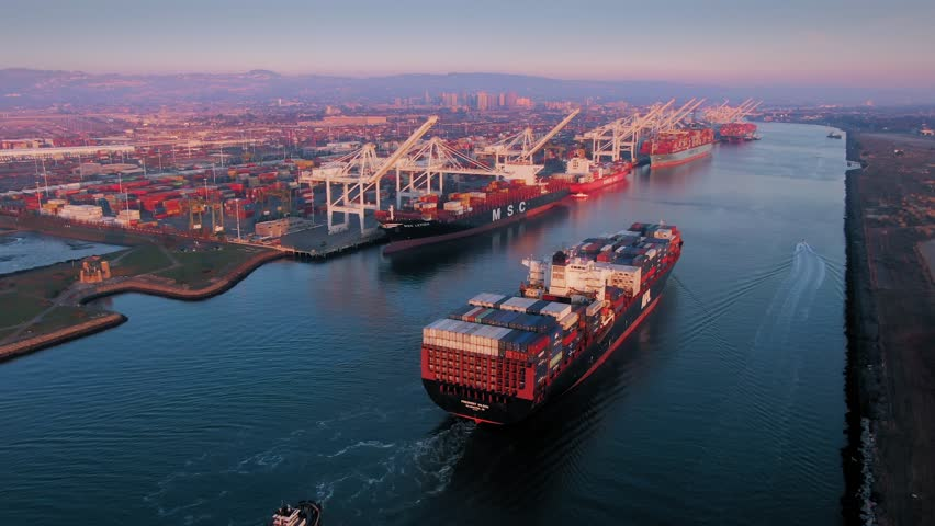 Aerial Of Container Ship sailing into the The Port Of Oakland at sunset, California, USA.