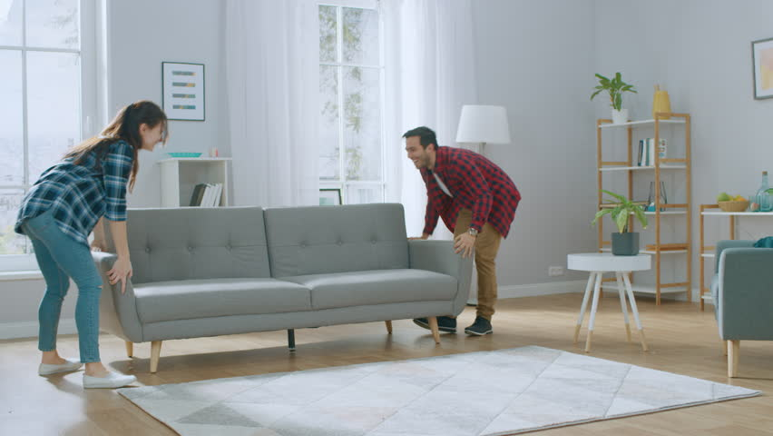 Happy Young Couple Moving New Couch into the Living Room, Fall on it to Rest. Bright Modern Apartment with Stylish Furniture. | Shutterstock HD Video #1022087902
