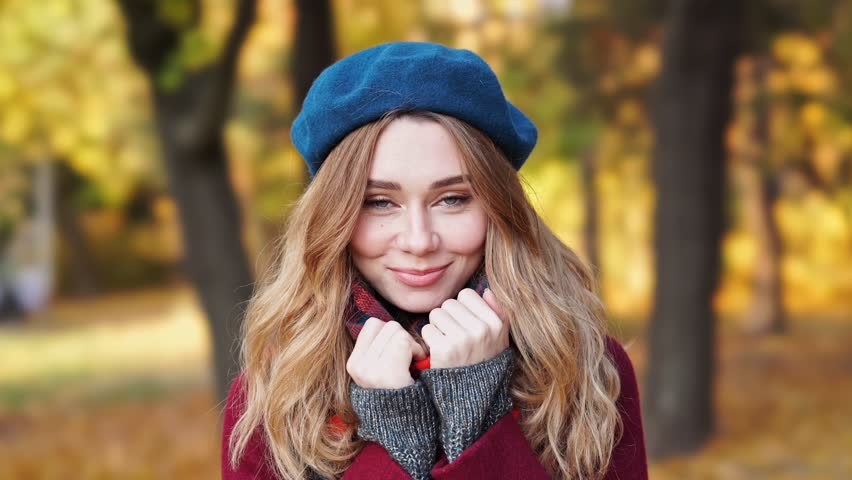 2a1bc8eb1ca28 Close up view of Smiling brunette woman in beret hat and coat looking at  camera while walks in park