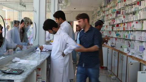 Swabi, Khyber Pakhtunkhwa PAKISTAN - October 17, 2018 - Pharmacist giving medicines in a busy medical store in Bacha Khan Medical Complex during morning hours in Swabi, Khyber Pakhtunkhwa Pakistan.