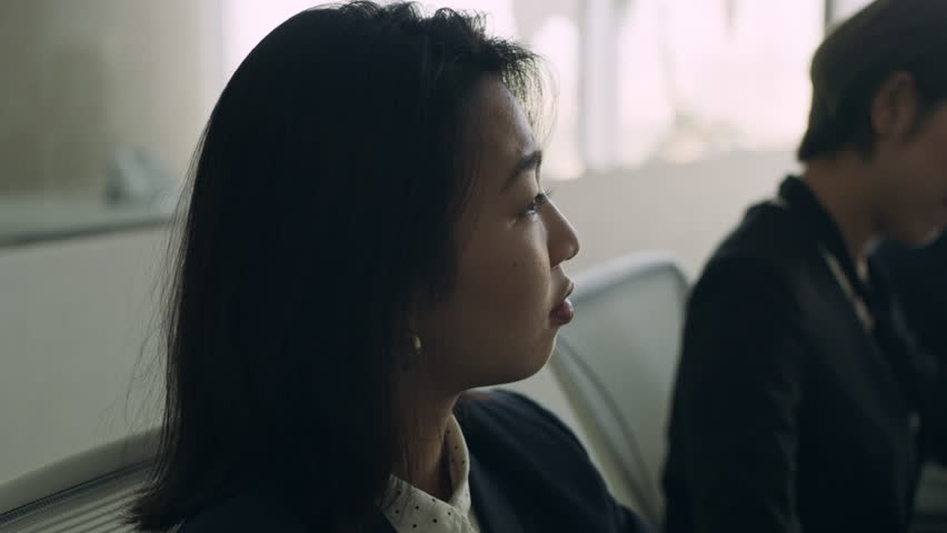 Medium shot on 4k RED camera. Group of Japanese business people work together in a meeting at a large conference room table in a modern office.