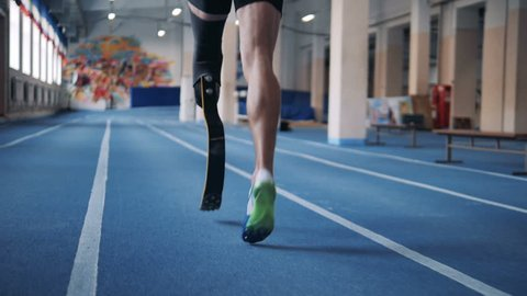 A runner training with prosthetic leg, back view.