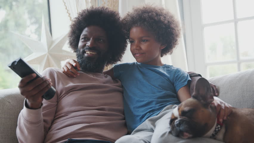 Smiling middle aged black father and pre teen son reclining on sofa together watching TV with their pet dog, dad holding remote control, low angle, close up | Shutterstock HD Video #1022137222