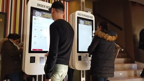 VALENCIA, SPAIN - JANUARY 9, 2019: McDonald's customers ordering food from a kiosk. McDonald's started rolling out kiosks in 2015 and by 2020 most McDonald's locations will have kiosks installed.